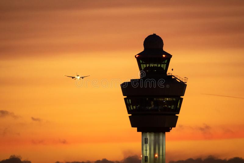 Amsterdam Schiphol International Airport control tower with a plane landing in the background during sunset stock photo