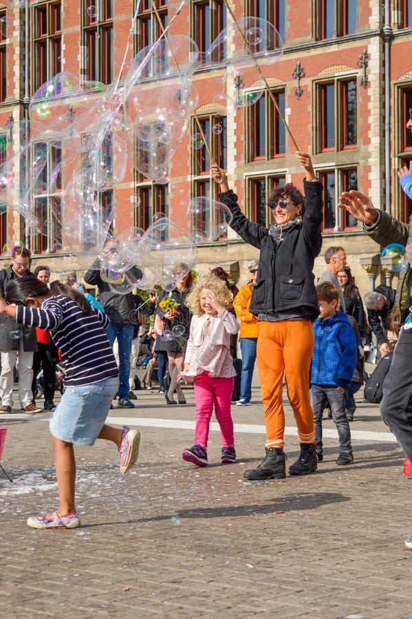 AMSTERDAM - SEPTEMBER 18, 2015: Kvinna som gör den enorma bubblan att svälla arkivbild