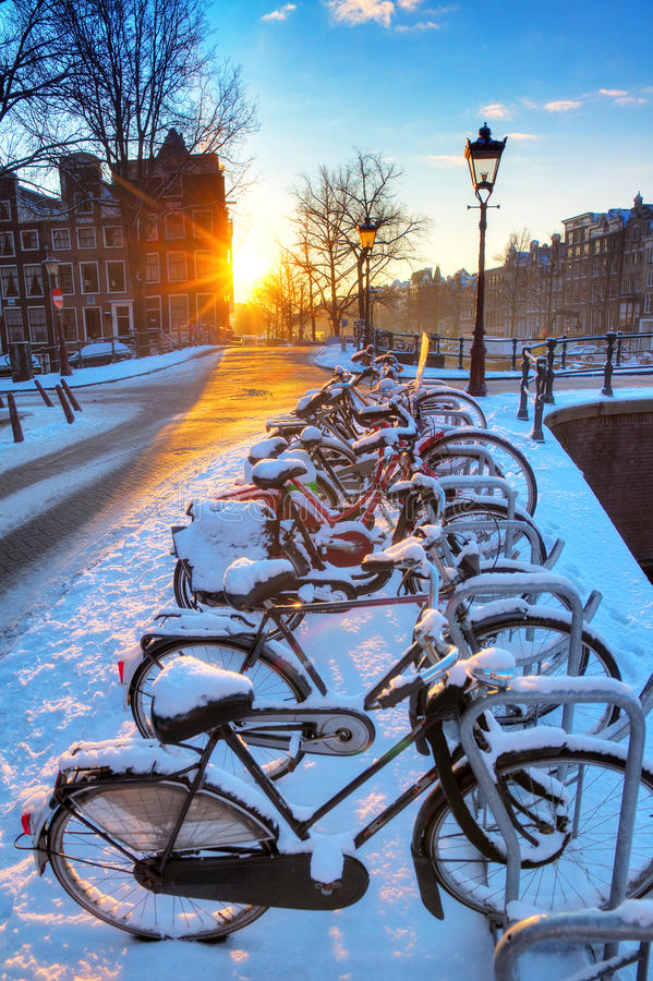 Amsterdam snow bicycles. Sunrise over the canal streets of Amsterdam, the Netherlands, with bicycles covered in snow on a beautiful winter day. HDR royalty free stock image