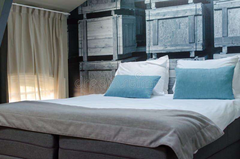 AMSTERDAM som ÄR NEDERLÄNDSK - Maj 2019: Hemtrevlig säng med den gråa överkastet och blåa kuddar i ett rum av en hyrd lägenhet i  arkivfoto