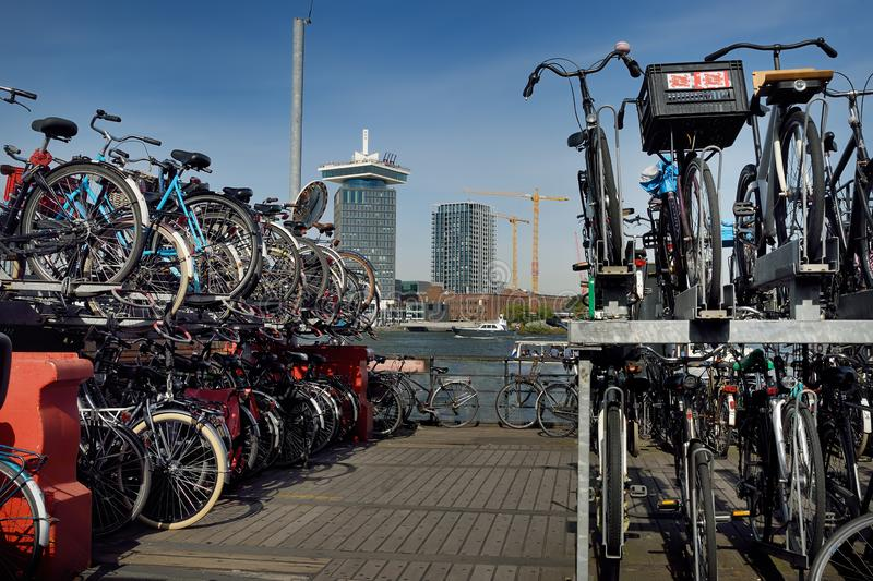 AMSTERDAM SOM ÄR NEDERLÄNDSK - SEPTEMBER 17, 2018: Cykelparkering på pir av floden hej i Amsterdam, sikt av floden och ett utkikt fotografering för bildbyråer