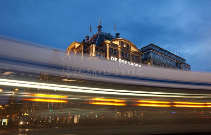 Amsterdam spårvagn som förbigår De Bijenkorf i fördämningfyrkant arkivbilder