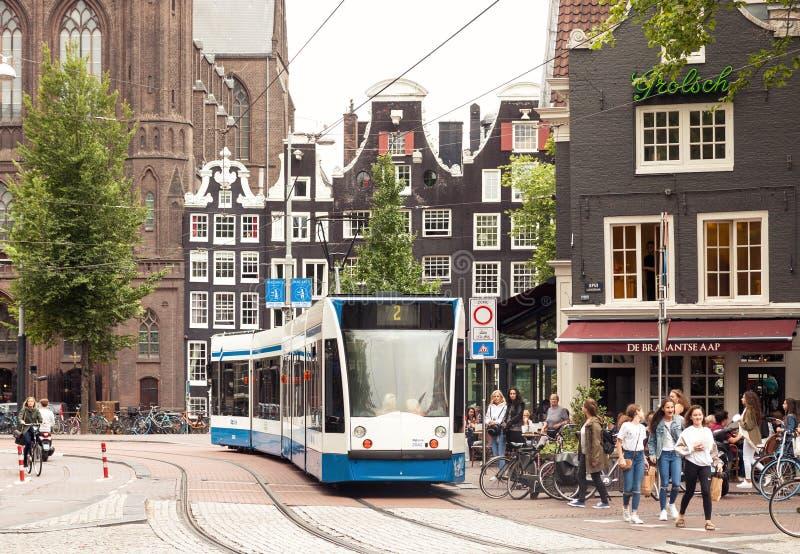 Amsterdam-Stadtzentrum-Straßenansicht mit der Leute- und Transporttram, die vorbei überschreitet stockfotos