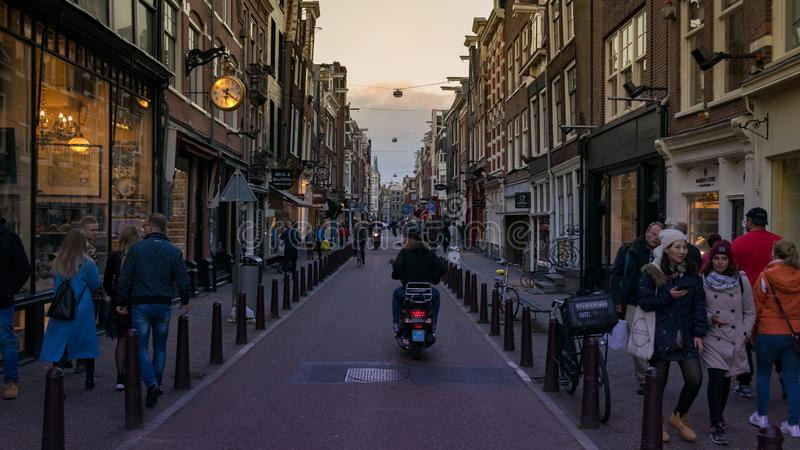 Amsterdam streets with people walking and men in bike royalty free stock photo