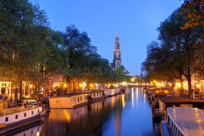 Amsterdam twilight. Night scene of Prinsengracht Canal in Amsterdam (The Netherlands) with the spire of Westerkerk and full moon. The over-exposed original moon