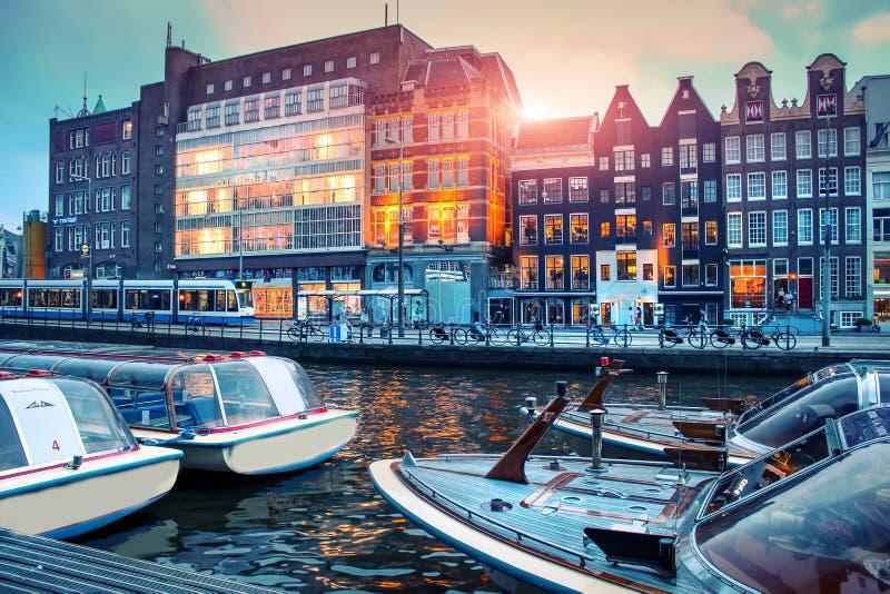 amsterdam, zachód słońca Łodzie w Amstel rzece w Amsterdam w wieczór przy zmierzchem Pejzaż miejski Europejski miasto w lecie fotografia royalty free