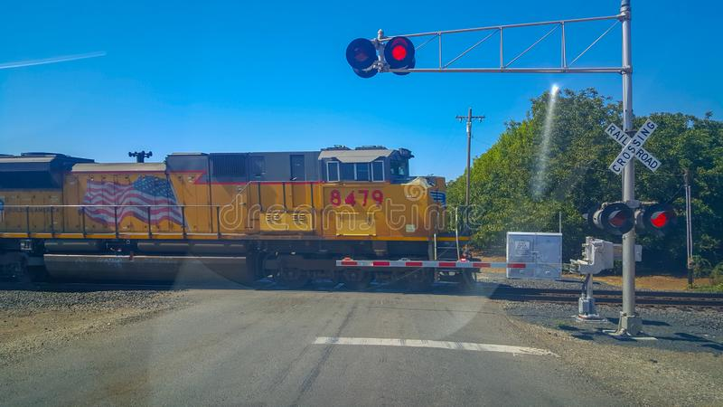 Amtrak train passing road bells barrier red light. Chico, United States - September 18, 2015 : An AMTRAK cargo train is passing a rail crossing between Chico and stock photography