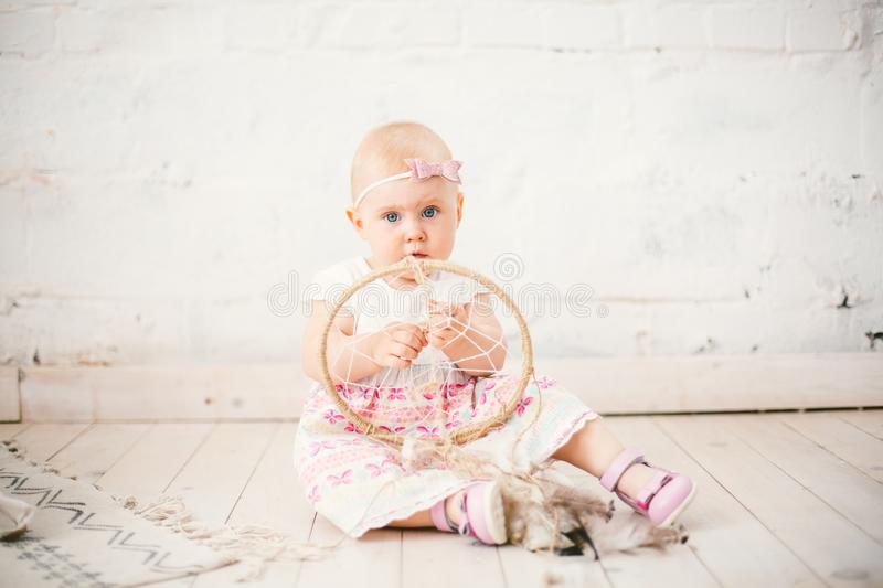 Amulet dream catcher and little baby girl one year with blue eyes, blonde sits on the floor in a dress and holds an royalty free stock photography