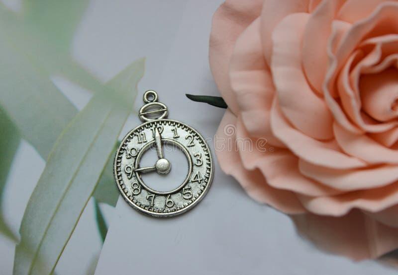 Amuleto de plata bajo la forma de cara de reloj en un fondo blanco foto de archivo libre de regalías