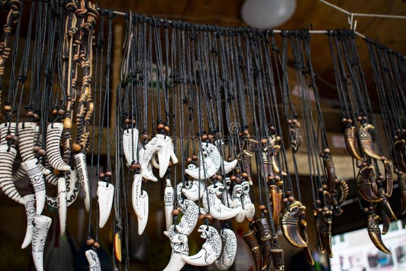 Amuletos do osso cinzelados em uma corda preta fotos de stock royalty free