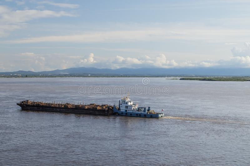 On Amur River, tugboat pushes barge with forest. On the Amur River, a tugboat pushes a barge with a forest stock images