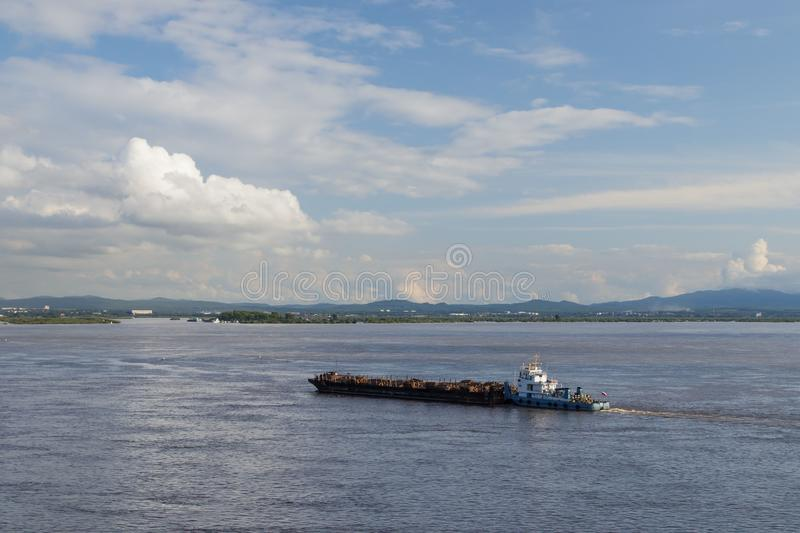 On Amur River, tugboat pushes barge with logs. On the Amur River, a tugboat pushes a barge with logs stock image