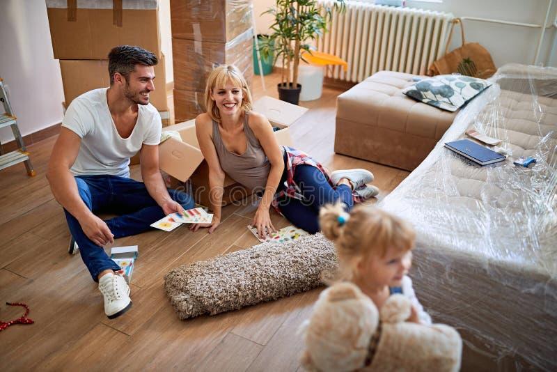 Amusant déménager dans une nouvelle maison - les parents déplacent les caisses dans une nouvelle maison photographie stock libre de droits