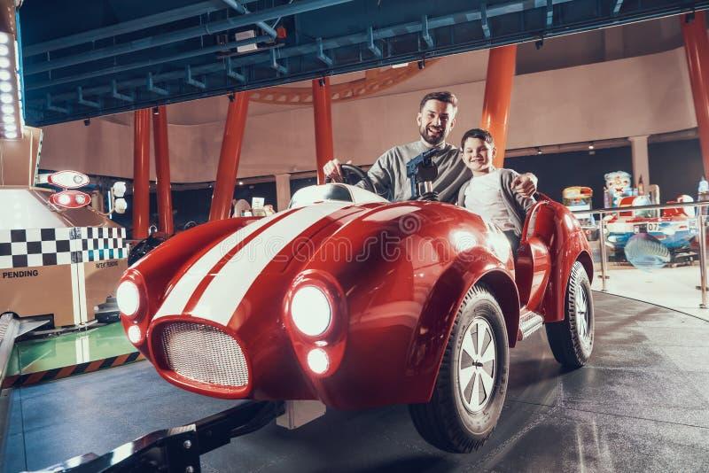Amused微笑的父亲和儿子坐玩具汽车 免版税库存照片