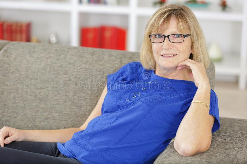 Amused attractive blond woman sitting on sofa royalty free stock photo