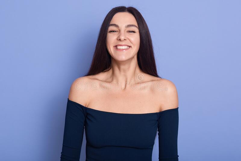 Amused beautiful young woman wearing dress posing with bare shoulders and looking directly at camera, brunette female with royalty free stock photography