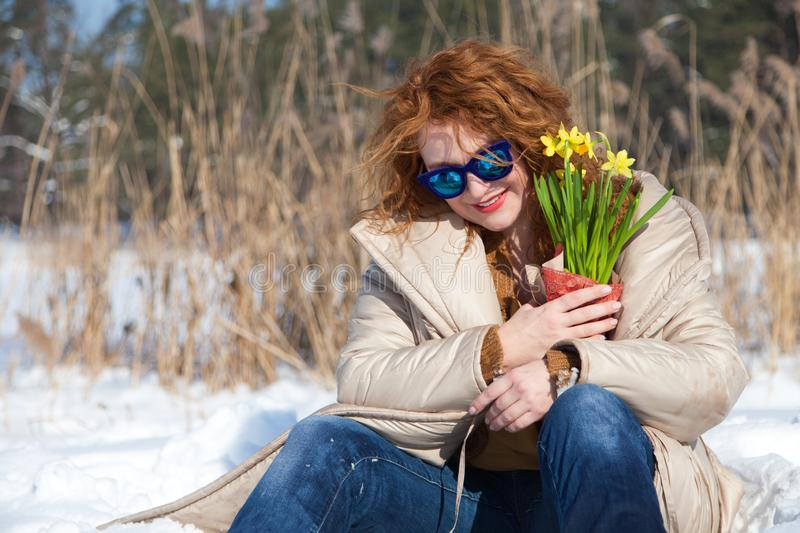 Amused charming woman with blue sunglasses resting in snow while looking down stock photo