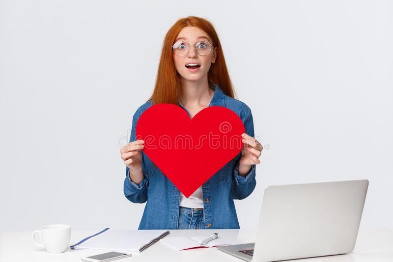 Amused and dreamy surprised redhead girl received big red valentines day heart from coworker, standing near working royalty free stock photo