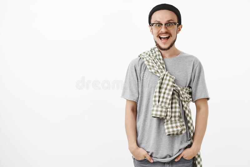 Amused and entertained handsome stylish hipster man with beard in glasses and black beanie with checked shirt crossed on royalty free stock images