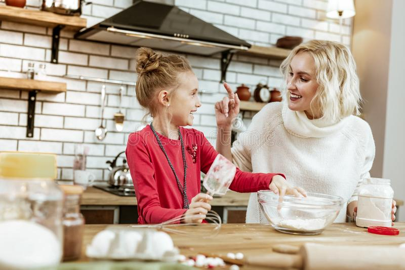 Amused good-looking blonde mother having fun with baking ingredients royalty free stock image
