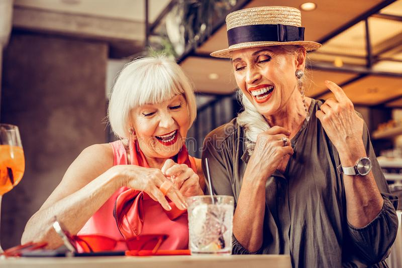Amused good-looking old ladies being excited while drinking together royalty free stock images