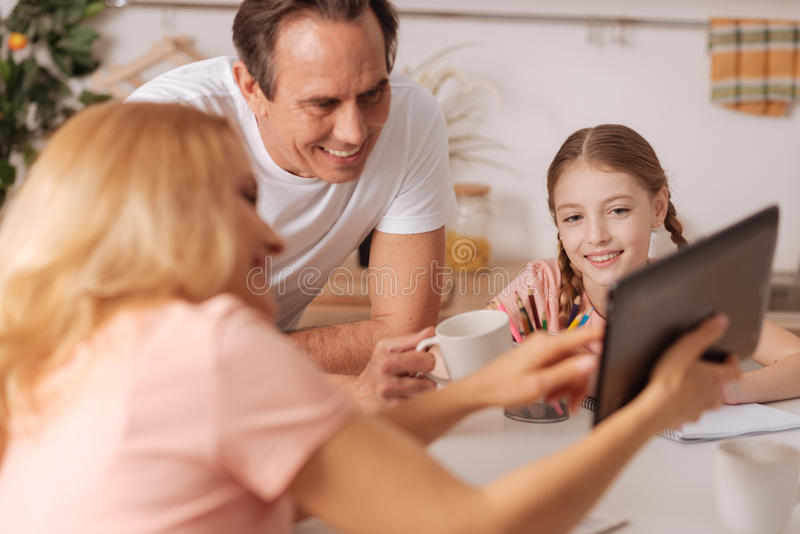 Amused mother enjoying new gadget with family at home stock image