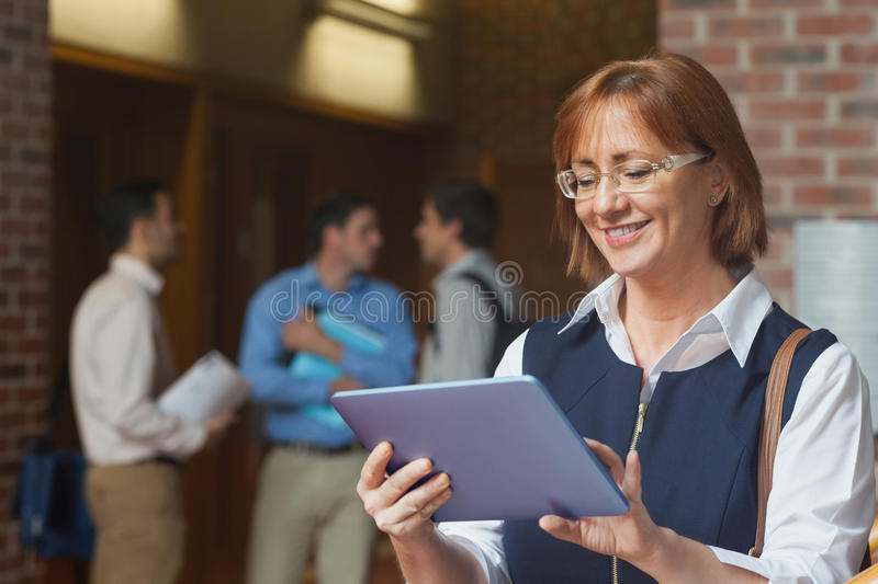 Amused smiling mature woman using her tablet royalty free stock photography