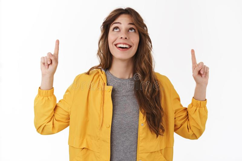 Amused wondered cute young 25s girlfriend look up smiling cheerful pointing upwards mesmerized fascinated awesome copy stock photo
