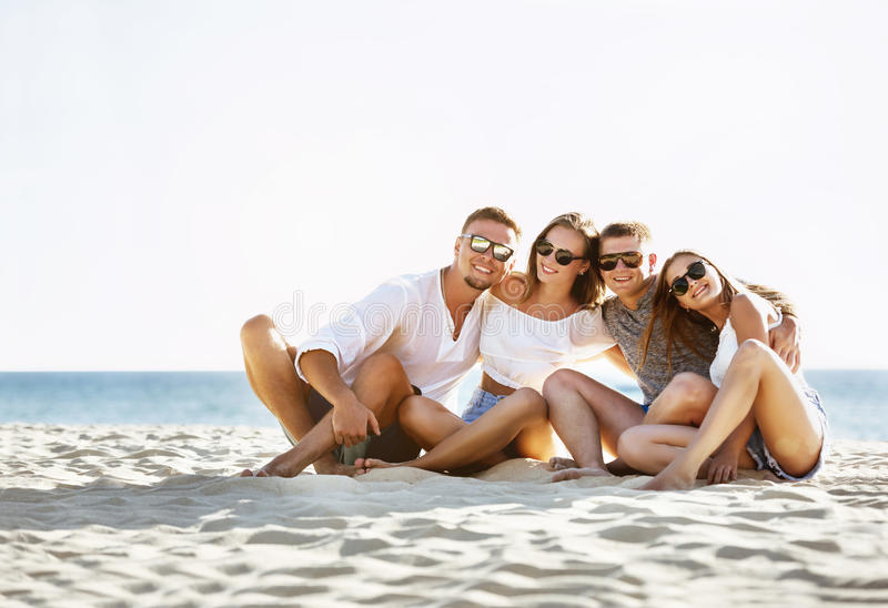 Amusement d'amis du groupe quatre sur une plage photographie stock