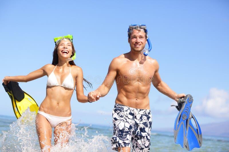 Amusement de couples de plage dans naviguer au schnorchel riant de l'eau photo libre de droits