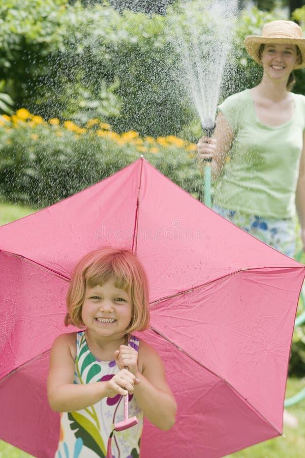 Amusement de l'eau d'été avec la pluie de boyau de jardin image libre de droits