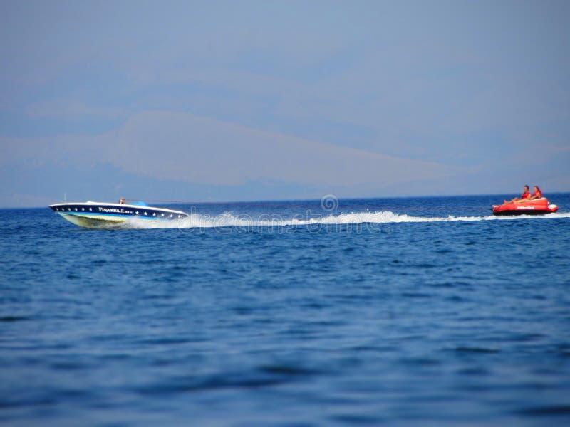 Amusement de l'eau sur le bateau de banane Vacances d'été par la mer La belle eau bleue lumineuse et bateau rouge et blanc et ban photos stock