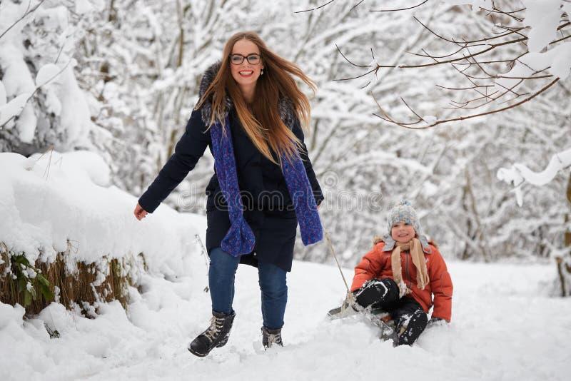 Amusement de l'hiver une fille et un garçon sledding images stock