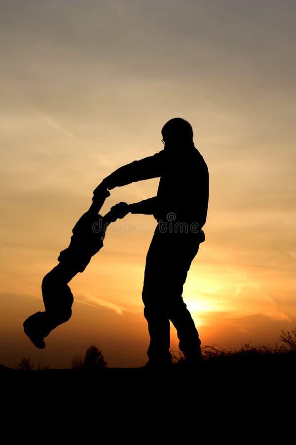 Amusement de père et d'enfant dans le coucher du soleil photo stock