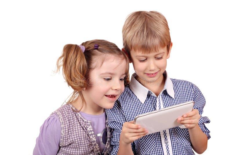 Amusement de petite fille et de garçon avec la tablette photographie stock libre de droits