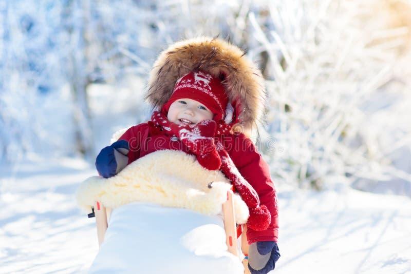 Amusement de traîneau et de neige pour des enfants Bébé sledding en parc d'hiver images libres de droits