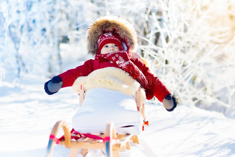 Amusement de traîneau et de neige pour des enfants Bébé sledding en parc d'hiver photos libres de droits