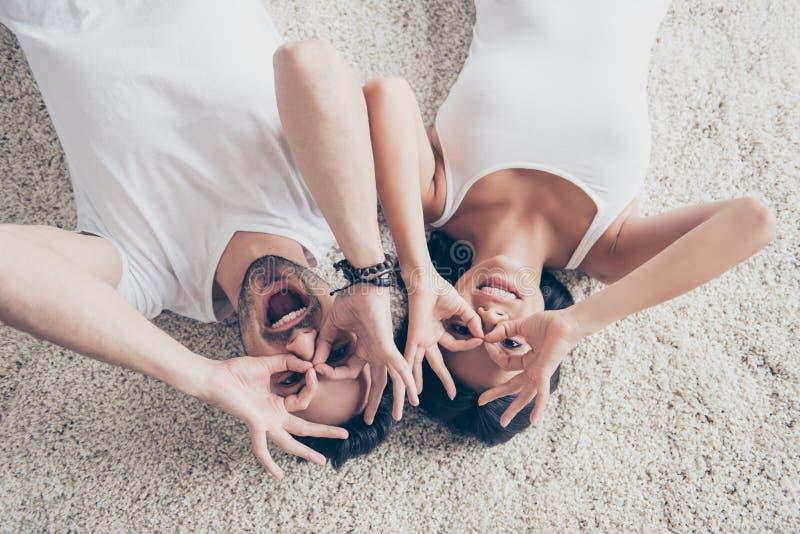 Amusement ensemble Le couple espiègle se trouve sur le plancher sur le comfortabl photographie stock
