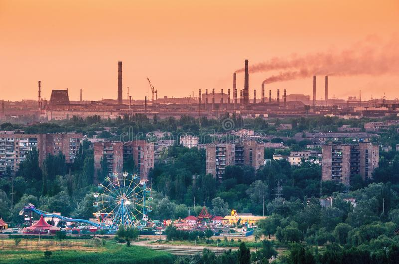 Amusement park with Ferris wheel and steel factory. Amusement park with Ferris wheel and buildings on the background of metallurgy plant with smog at sunset royalty free stock image
