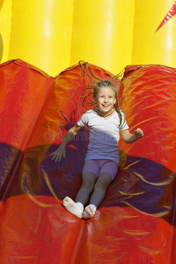 The amusement park. Girl slides down a hill on an inflatable stock photo
