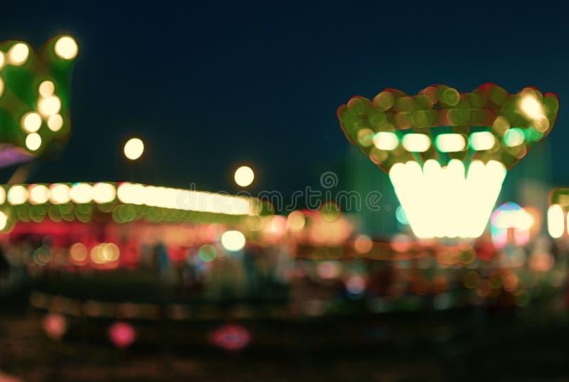 AMUSEMENT PARK at night in bokeh royalty free stock image