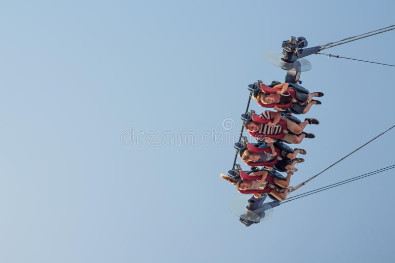 Amusement park ride. People in slingshot, clear blue sky, Prater Vienna Austria, 26 August 2017 stock photo