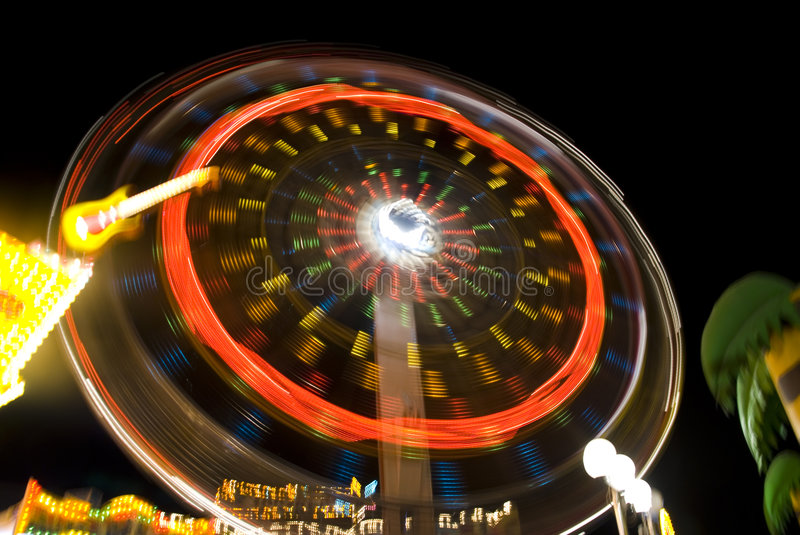 Amusement ride. A brightly coloured whirring amusement park ride with neon colours in background stock image