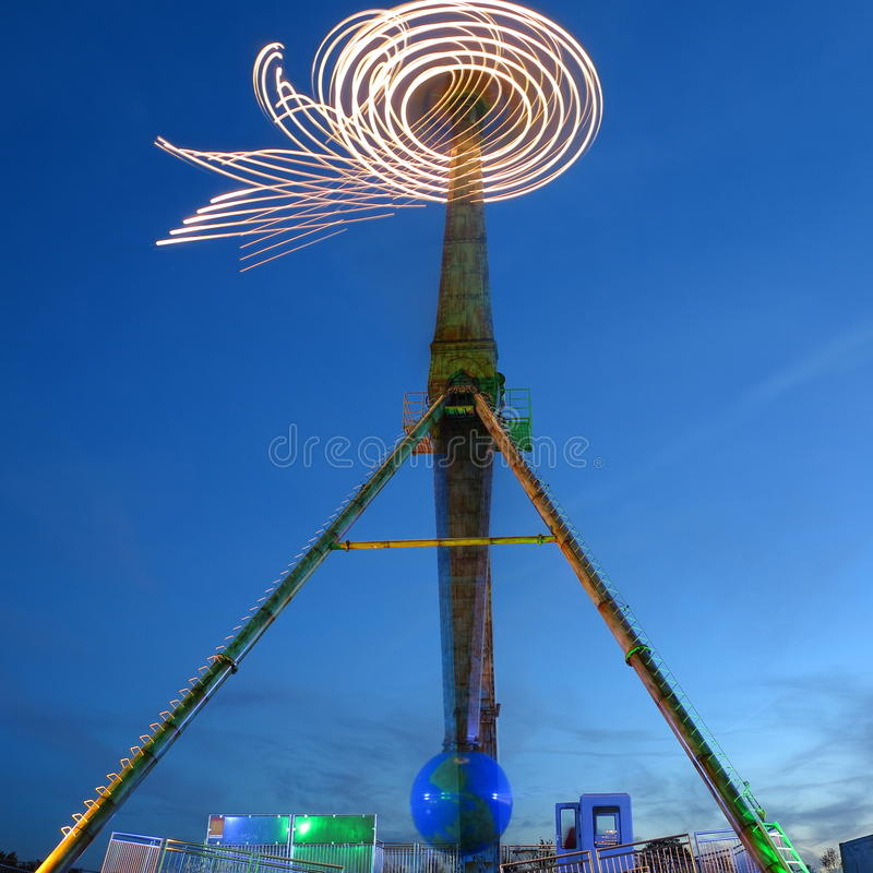 Amusement ride rotation blur at blue hour. The blurred illustration of a spinning sky jet ride - long exposure at the blue hour stock photos