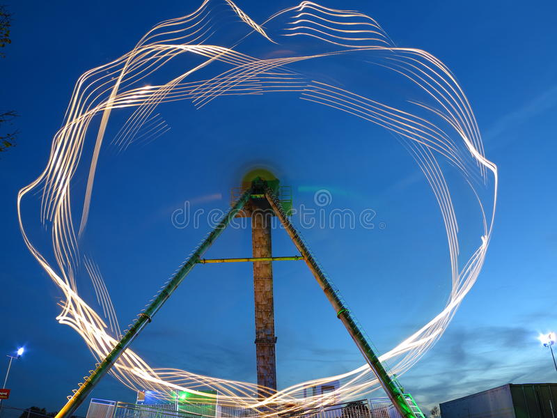 Blurred light of spinning ride at dusk. The blurred illustration of a spinning sky jet ride. Long exposure at the blue hour royalty free stock photography