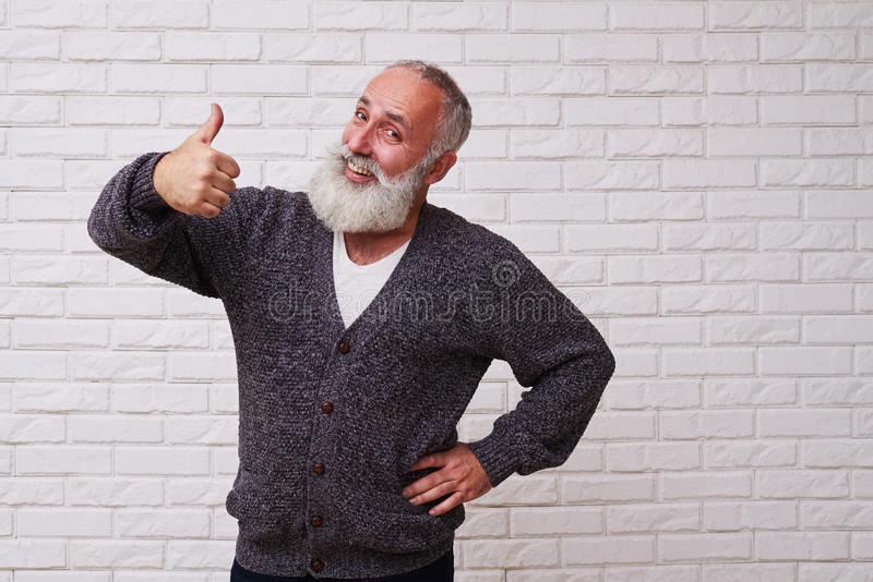 Amusing beard man holding his thumb-up royalty free stock photos