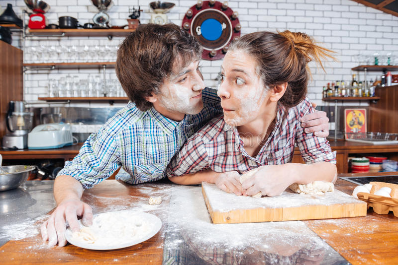 Amusing couple making funny faces on kitchen together. Amusing young couple with flour on faces making funny faces on the kitchen together royalty free stock photography