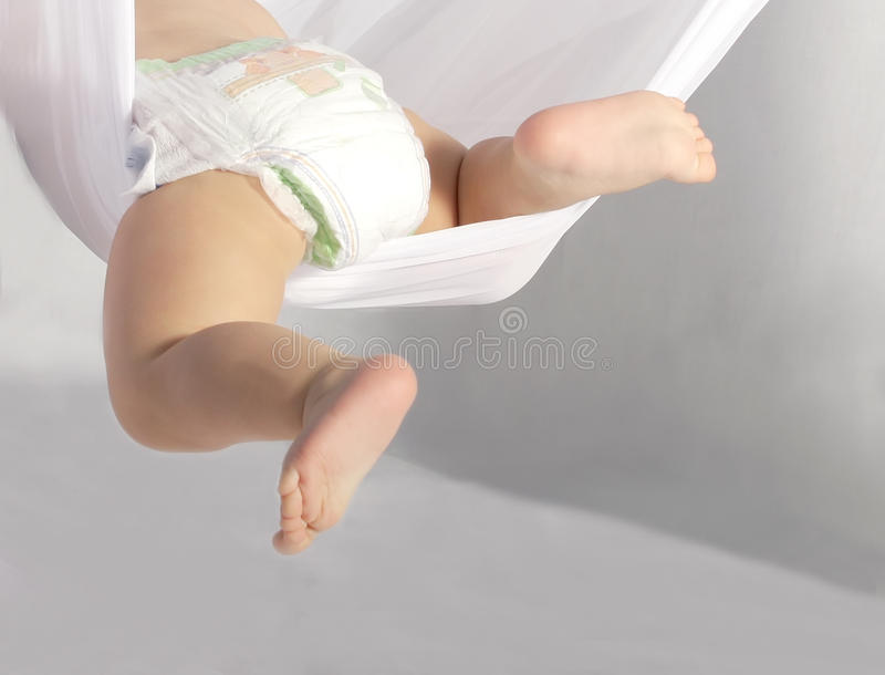 Amusing gentle legs of the kid in a white hammock stock images