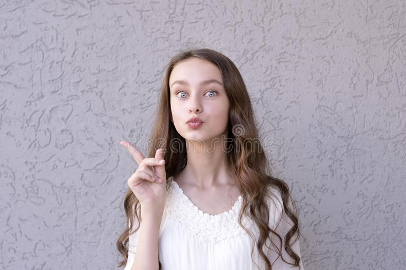 Amusing girl with open-eyed. Portrait of surprised teenager showing something by hand. Astonished female pointing finger or demonstrating goods or products stock photo