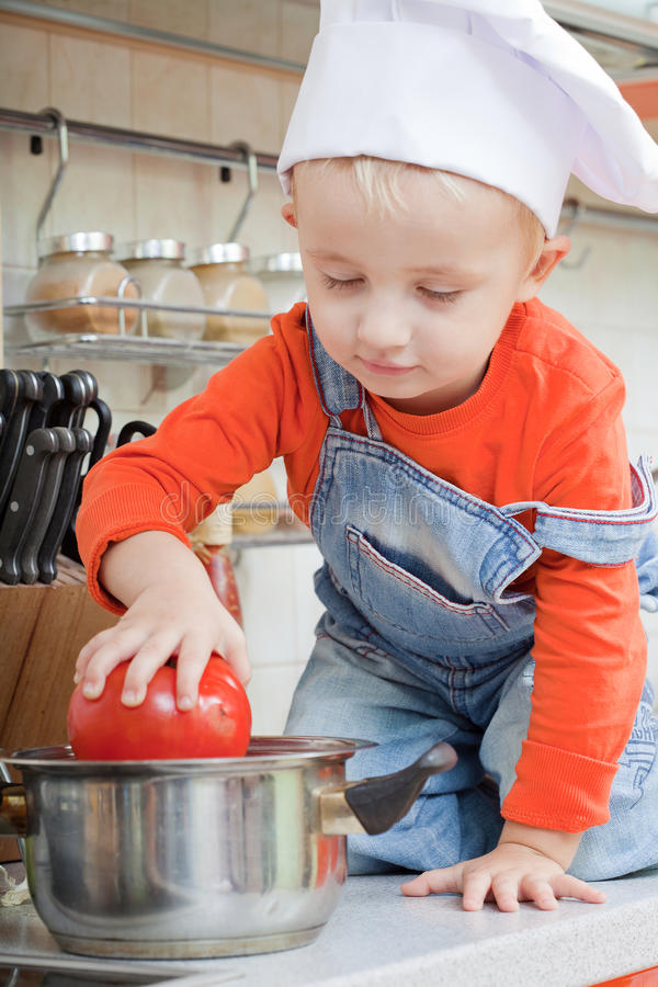 Amusing kid in a cook cap